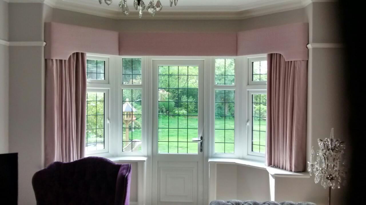 Classic shaped bay window pelmet with matching curtains in a plain silk fabric.