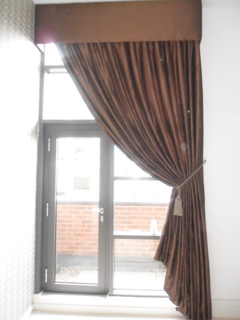 Add real drama to a very tall window with this oversized fabric covered pelmet. With a single curtain scooped back into a large tassel rope tie back.