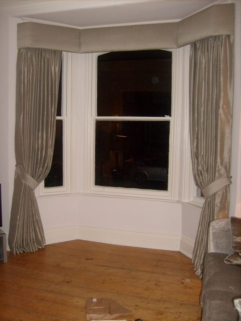 Classic looking bay window pelmet covered with silk fabric. This gives a simple understated look to this Victorian bay window.